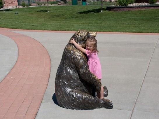 Nena abrazando a una estatua de oso