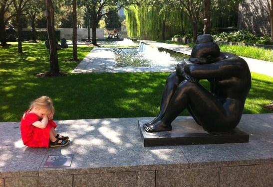 Nena junto a una estatua